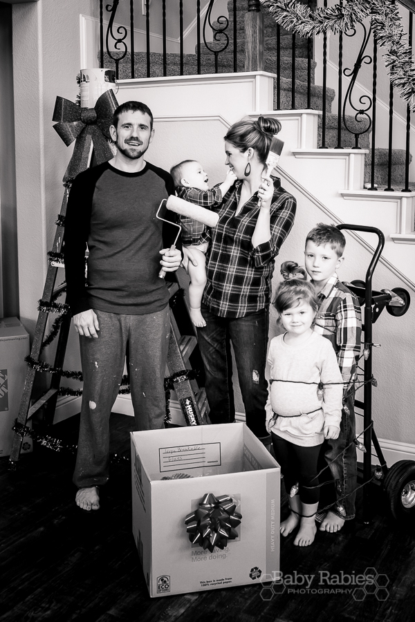 Christmas Moving Announcement- Decorate a ladder with tinsel, bows and a paint can. Stage some moving boxes with bows. Tie the kids to the dolly with lights. Pose with paint brushes! | BabyRabies.com