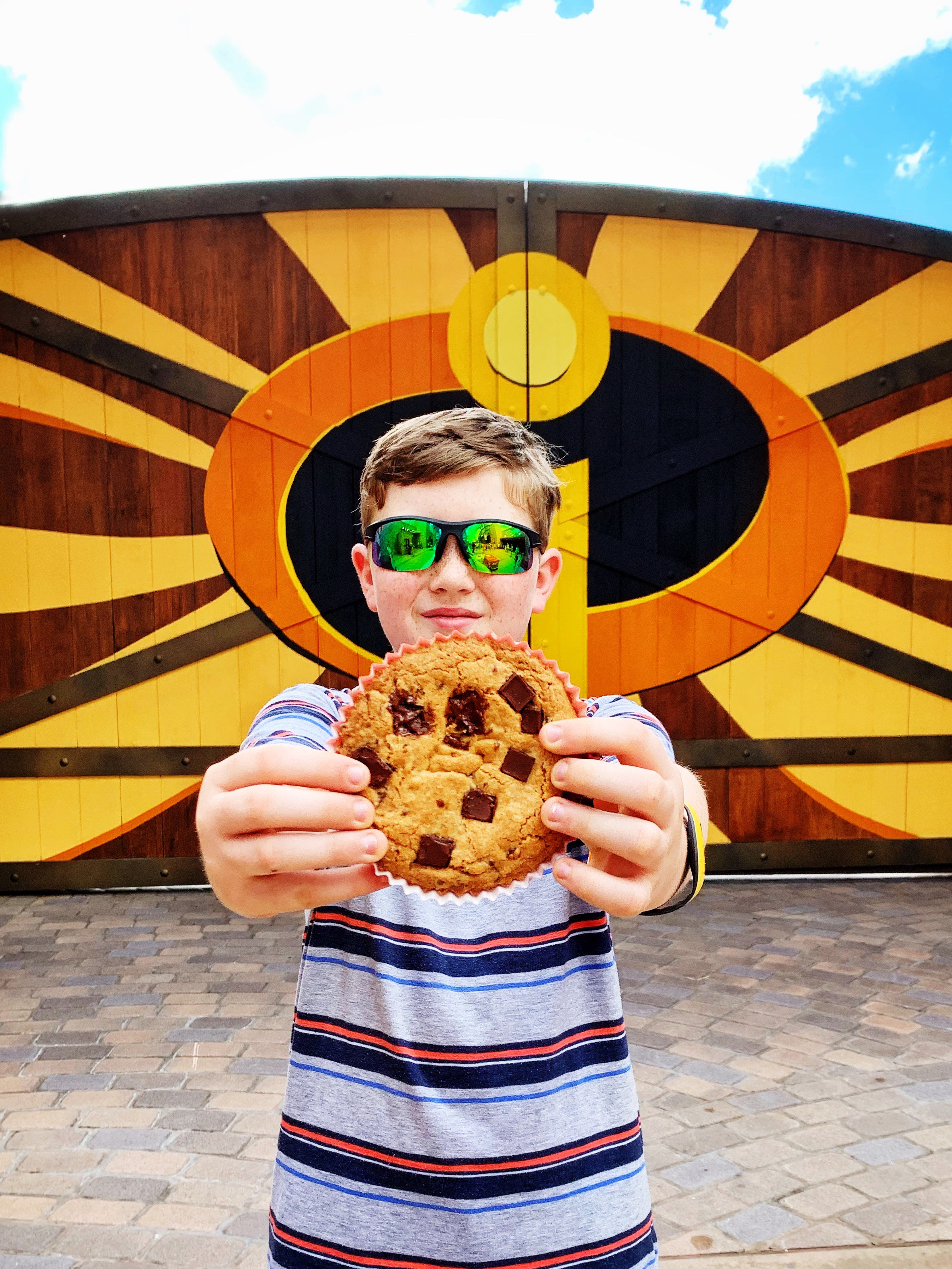 image of kid posing in front of Incredible sign with a cookie